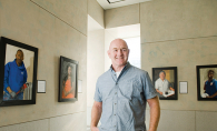 Artist Joe Burns stands before portraits in his gallery, Facing America.