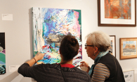 Two women examine a painting at St. Louis Park Friends of the Arts