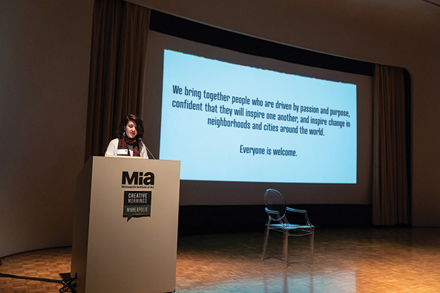 An event volunteer reads the Creative Mornings manifesto at Minneapolis Institute of Arts.