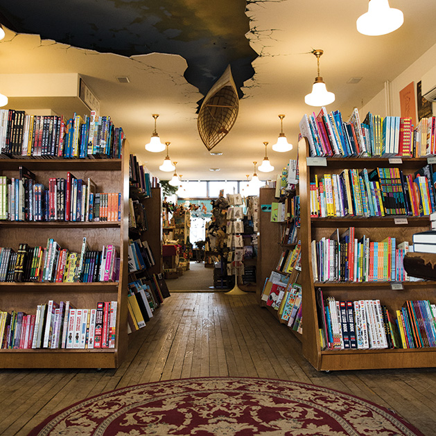 The bookshelves at Wild Rumpus. Above, a boat is affixed to the ceiling.