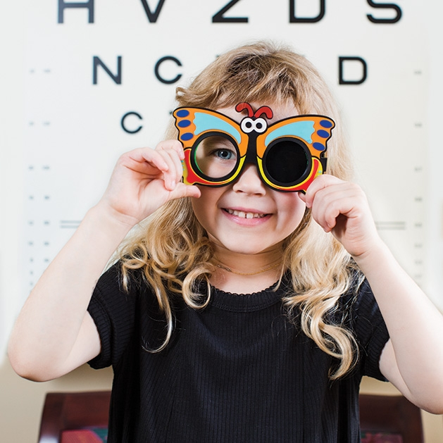 A girl holds a pair of glasses, courtesy of the E.Y.E. Community Initiative.