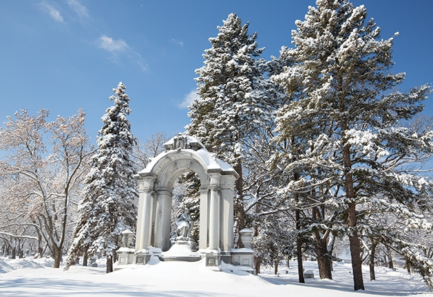 A monument at Lakewood Cemetery covered in snow.