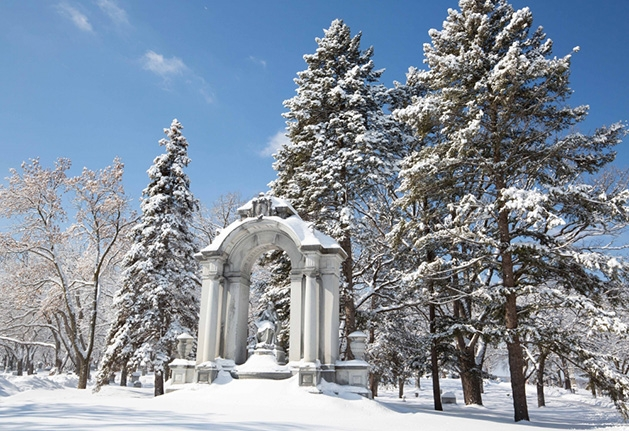 A memorial covered in snow and surrounded by trees in Lakewood Cemetery