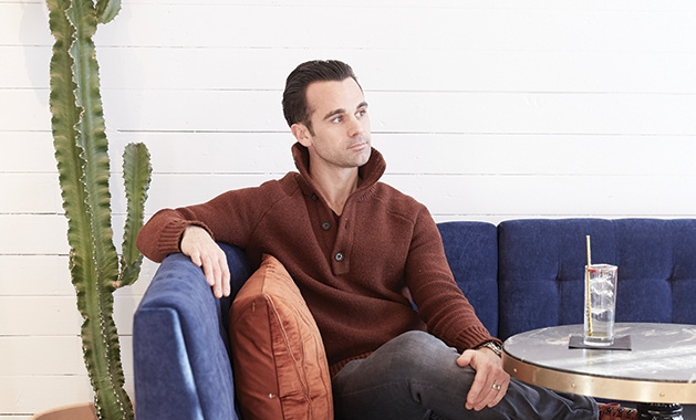 Ben Brueshoff, owner of BET Vodka, sits on a blue couch with a drink nearby/
