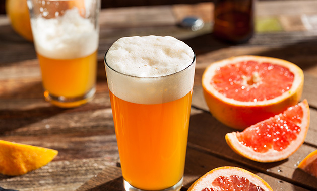 A local summer beer sits on a patio table next to a grapefruit.