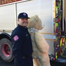 A volunteer with Firefighters for Healing holds a giant teddy bear.