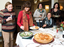 Members of a cooking club gather around a meal.
