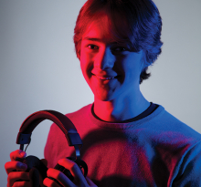 An E Sports athlete holds a gaming headset.